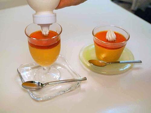 カラメルをスプーンでかぼちゃのプリンに重ねて、ホイップクリームを飾る