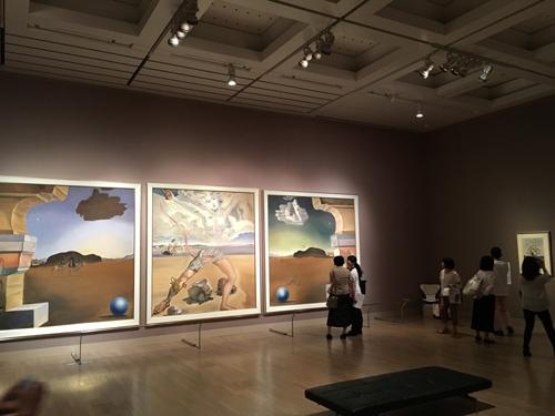 ダリ展会場風景。左から順にサルバドール・ダリ 《幻想的風景 暁》《幻想的風景 英雄的正午》《幻想的風景 夕べ》(ヘレナ・ルビンスタインのための壁面装飾)(=3連作、1942年、249.0×243.0cm、251.0×224.0cm、247.5×247.0cm、カンヴァスにテンペラ、横浜美術館蔵  © Salvador Dalí, Fundació Gala-Salvador Dalí, JASPAR, Japan, 2016. )