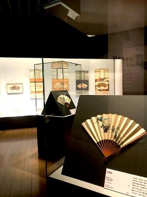 サントリー美術館「扇の国、日本」展会場風景。一番手前の作品は鈴木其一の《朝顔図》(太田記念美術館蔵)。会場には、扇だけでなく扇を貼り付けたりかたどったりしたさまざまな種類・技法の作例が並ぶ
