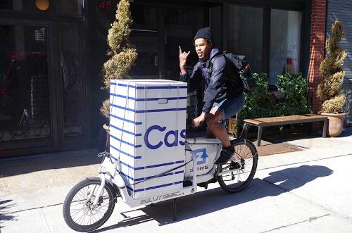 写真3●自転車でマットレスを運ぶ配達員
