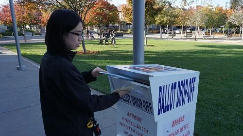 写真●米クパチーノ市役所前で投票する女性