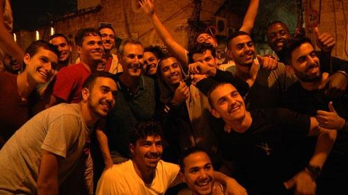 いまだ衰えることのない人気を博すユリ・ゲラー。地元テルアビブにて、観光客の青年たちに声をかけられ写真を撮る
