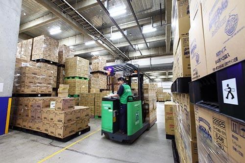メーカーの工場などからトラックで運びこまれてきた日用品の段ボールが、1階に積み上げられていた。