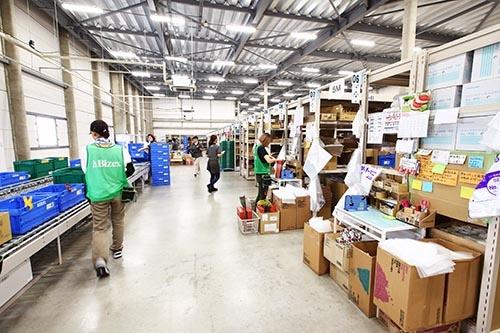 発注頻度の高い商品は、従業員が手作業でピッキングする。屋内はLED照明完備で明るいが、窓が多いわけではない。