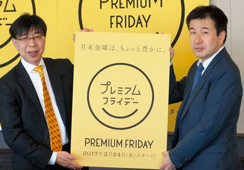 プレミアムフライデーのロゴを発表する経産省の林課長(左、写真=朝日新聞社/時事通信フォト、2016年12月)