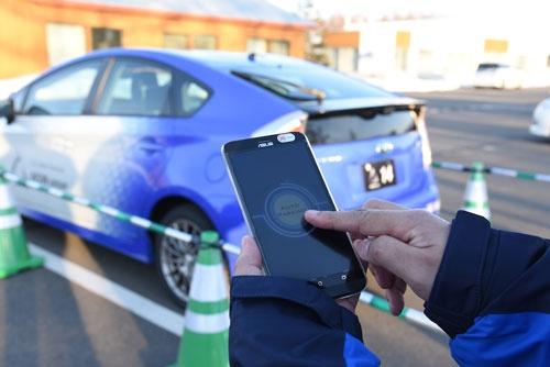 アイシン精機が開発中の自動駐車システム。スマートフォンのボタンを押すと、無人で駐車できる