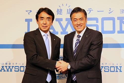 3月28日、会見後に固く手を握ったローソンの竹増貞信副社長(左)と玉塚元一社長(撮影:都築雅人)