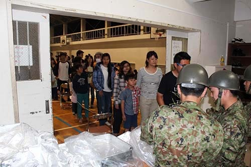 日本人にまじって避難所での自衛隊の炊き出しに並ぶ外国人留学生。避難所の事務局からは「立命館アジア太平洋大の学生はマナーがいい」との声も (写真:大分合同新聞提供)