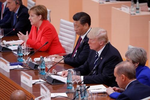 ハンブルクG20でメルケル議長の隣に席を並べた習近平主席とトランプ大統領だが、それぞれの狙いには埋めがたい違いが…(写真:ロイター/アフロ)