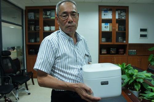 シャオミ傘下の純米電子科技で働く内藤毅氏。手にしているのはシャオミが今年3月に発売した炊飯器