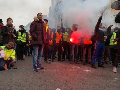 治安部隊と放水車の前で抗議する人々