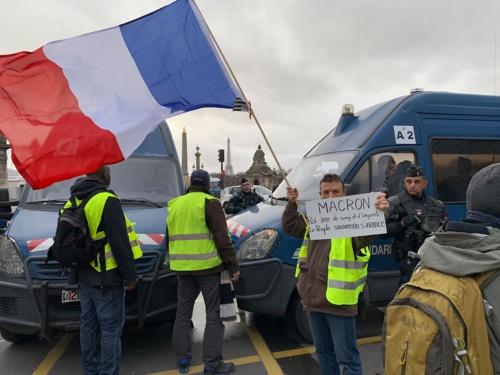 治安部隊の車両とエッフェル塔を背景に、フランス国旗を手に持つデモ参加者。報道陣のカメラを意識しているようだ