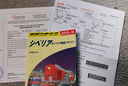 シベリア鉄道のEチケット(下右)と旅行確認書・バウチャー(下左)。ガイドブックの「地球の歩き方 シベリア」を買ったのはいいが、なんと旅行に持っていくのを忘れてしまった