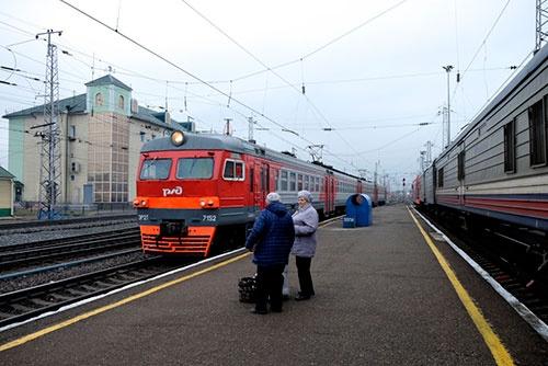 駅のホームで郊外電車の到着を待つ人。私たちの列車は右側