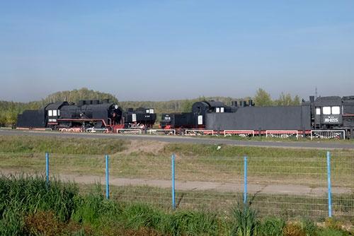 左端の機関車はかなりボイラーの直径が大きいユーモラスな形。その奥には軽便用か工事用と思われる機関車もちらりと見える