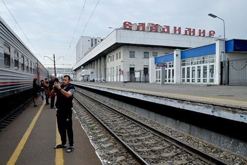 どこの国でも同じ。駅舎をバックにスマホで自撮りをするロシア青年