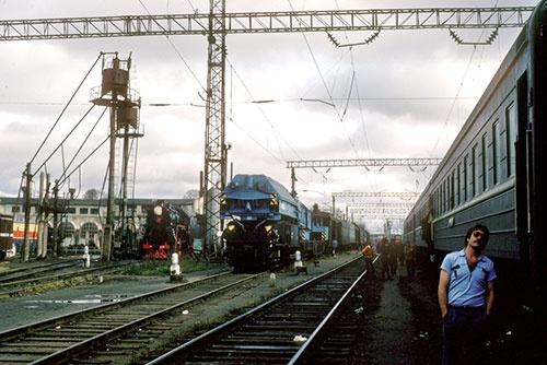30年前の長時間停車で撮った写真。どこの駅かは分からないが、左の車庫にちらりと蒸気機関車が写っている(1985年)