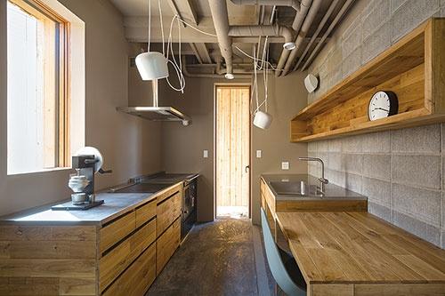 まきコンロを備えたキッチン。流し台の向こう側の壁内に、2階の浴室から排出する湯の熱を回収するパイプを組み込んでいる。写真の手前側に1000リットルの貯湯タンクを設置している(写真=Shinkenchiku-sha)