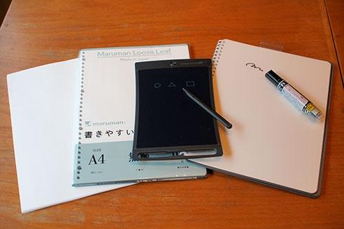 手書きの道具の例。左はA4のコピー用紙。ラフに書き散らしたいときに使う。左から2番目はA4サイズ無地のルーズリーフ。仕事用のノートとしても使い、保存したい場合にはバインダーに収める。中央にあるのが携帯型電子黒板「ブギーボード」(キングジム製)。上部に円形の消去ボタンがある。右は携帯型のノート型ホワイトボード「CANSAY ヌーボード」(欧文印刷製)。