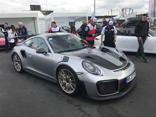 ポルシェ911の市販ラインアップにおいて、最速の位置づけとなる「GT2 RS」。最高出力 は700 PS。0 -100 km/h加速は2.8 秒、最高速度は340 km/h!<br /> 日本での車両本体価格は3656万円。ちなみに後ろに写っているのがトヨタドライバーの小林可夢偉選手、セバスチャン ブエミ選手、マイク コンウェイ選手。WEC第4戦の空き時間にポルシェの展示会場に見学に来ていた。3人とも興味津々の様子(写真:藤野)