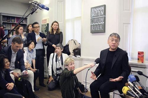 今年のノーベル文学賞の受賞が決まり、10月5日当日、記者会見で話すカズオ・イシグロ。記者も左側のメディア関係者の中にまぎれている。(写真:読売新聞/アフロ)