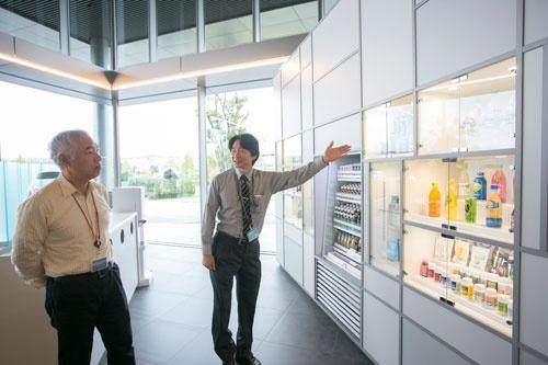 菅課長(右)が所属するサントリービジネスエキスパートは、グループ内の様々な事業会社に共通する業務を集約し、サポートする。まずは入口近くに設置されたガイダンススペースでサントリーの商品やセンターの概要のレクチャーから