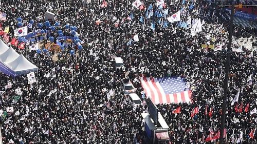 2月25日、保守派の集会は300万人を動員(主催者発表)、特大の星条旗も持ち込まれた。朴槿恵大統領の弾劾を求める集会との衝突が懸念されている(写真:AP/アフロ)