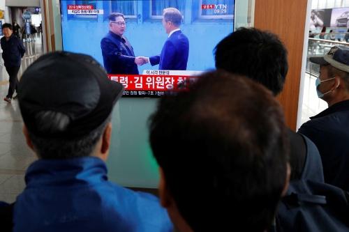 南北首脳会談の様子を報じるソウル駅の街頭テレビに見入る人たち(写真:ロイター/アフロ)