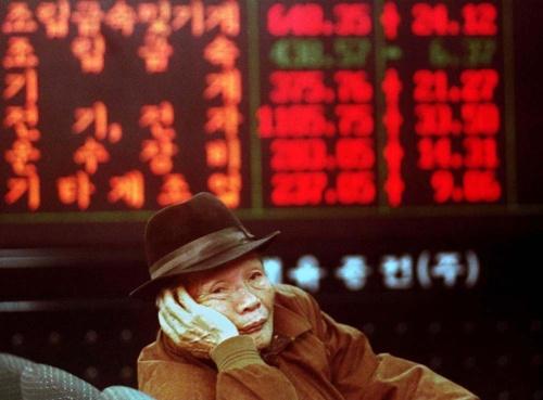 1997年12月、通貨危機に見舞われた韓国・ソウルで、株価ボード前に座り込んで疲れた表情を見せる投資家の男性(写真:ロイター/アフロ)