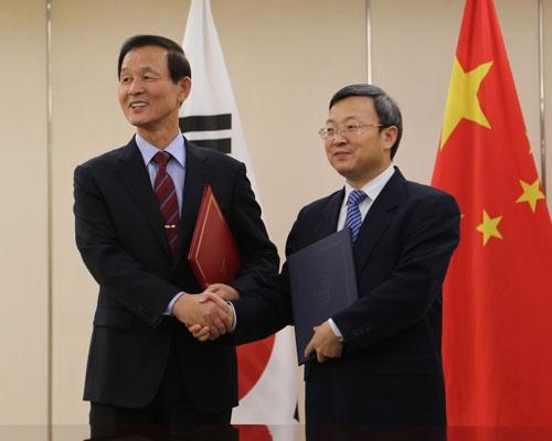 2015年12月、北京で中韓FTAの覚書を交換する金章洙駐中大使(左)。国防長官経験者が駐中大使に就くのは異例で、米国の軍事情報に関心を持つ「中国の期待」に応える人事だったと言われる(写真:YONHAP NEWS/アフロ)
