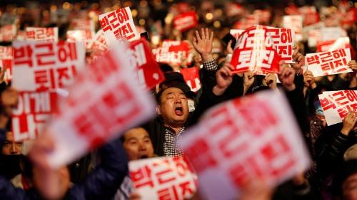 「朴槿恵退陣」のプラカードを手にソウルのデモに集まった人々(写真:ロイター/アフロ)