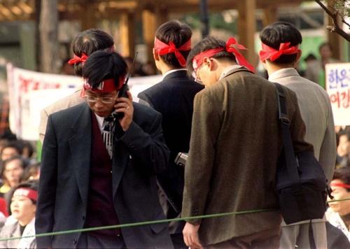 通貨危機に見舞われた韓国ソウルで1997年11月、金融改革方針を巡る反政府集会に参加した韓国銀行の行員たち(写真:ロイター/アフロ)