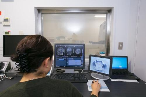 MRIを使う四本さん。本体はガラスの向こうの部屋にあり、川端さんが台の上で横になっている。
