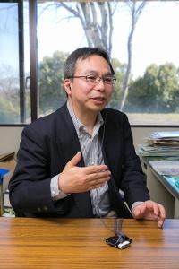 国立歴史民俗博物館准教授の山田慎也さん。机の上にある補聴器を使って取材に応じてくれた。