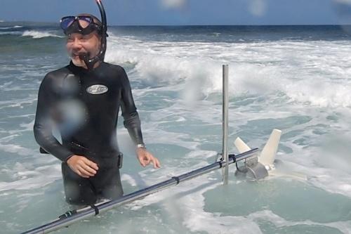 ウェットスーツを着込み、波力発電機の予備実験をしに自ら恩納村の真栄田海岸で海に入る新竹さん。