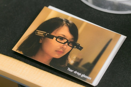 「涙眼鏡」を試す女性。