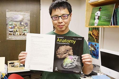 自分の論文の画像が使われた表紙を手にする宮下哲人さん。(写真提供:川端裕人)