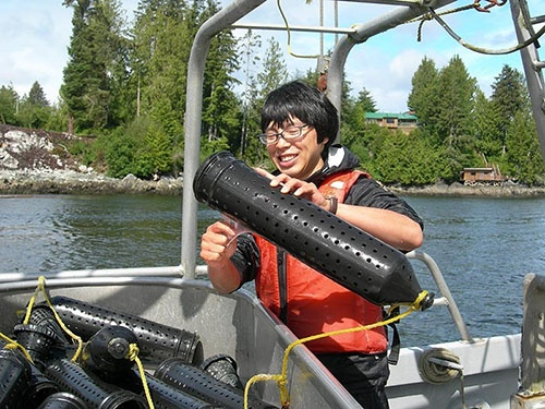 2010年、カナダ西海岸のバンクーバー島沖でヌタウナギを収集する宮下さん。ヌタウナギの粘液がカゴから手に伝わっている。(写真提供:宮下哲人)