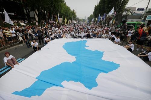 北朝鮮は、統一旗を先頭に南北合同で入場行進する目論見だ(写真:AP/アフロ)