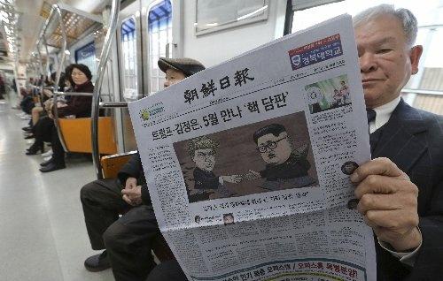 米朝首脳会談の決定を報じる新聞を読む韓国の市民( 写真:AP/アフロ)
