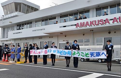 横断幕を手に2代目みぞか号ATR42-600を出迎える天草エアラインの客室乗務員ら