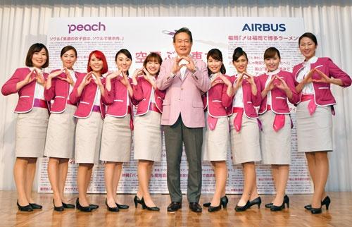 就航5年目の会見で、客室乗務員らと「ピーチポーズ」を取る井上CEO