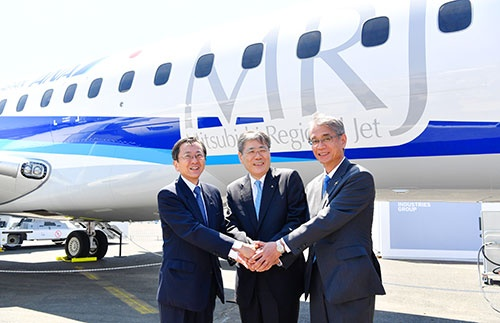 パリ航空ショーで展示されたANA塗装をまとったMRJの前で握手を交わす三菱重工の宮永社長(中央)と三菱航空機の水谷社長(右)、ANAホールディングスの篠辺副会長