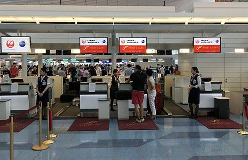 羽田空港のファーストクラスカウンター。赤いマットが敷かれ、高級感を演出している