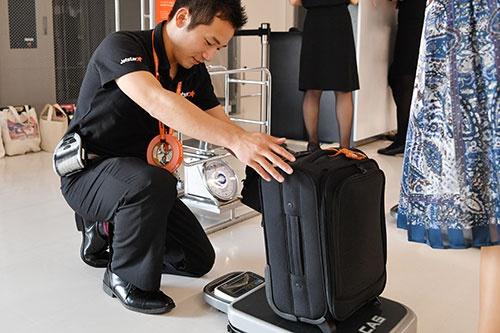 乗客一人ひとりの機内持ち込み手荷物の重さを量るジェットスター・ジャパン