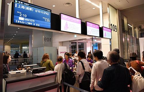ピーチの上海行き初便に搭乗する乗客たち。深夜なのに羽田空港の搭乗口前には行列ができていた