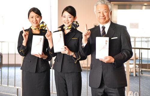 客室乗務員とポーズを取るスカイマークの佐山展生会長。国際線チャーター便への挑戦を前倒しするなどして企業価値を高めていく