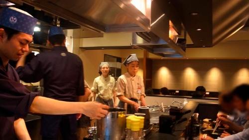 厨房を囲むようにして配置された客席からは調理をする様子がよく見えます。奥には落ち着いて食べられるテーブル席も。スタッフの制服は法被。和食割烹の雰囲気です。
