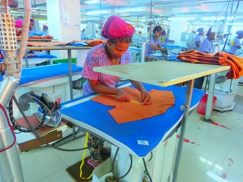 縫いあがったTシャツのポケットのサイズを確認する現地ワーカー(エチオピアの工場にて筆者撮影)