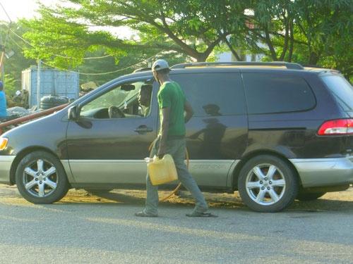 原油の精製を他国に頼っているナイジェリアでは、外貨不足によりガソリン不足にも陥っている。ガソリンスタンドの半分は開店休業中で、開店していても6時間程度並ぶ。路辺にはガソリンを2~3倍の価格で転売する人たちがいる(ナイジェリアにて筆者撮影)